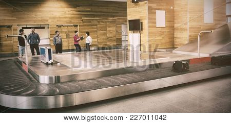 People standing by baggage claim in airport
