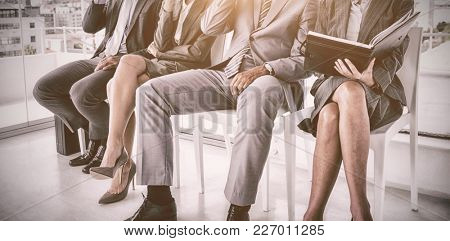 Well dressed business people waiting to be called for interview in office
