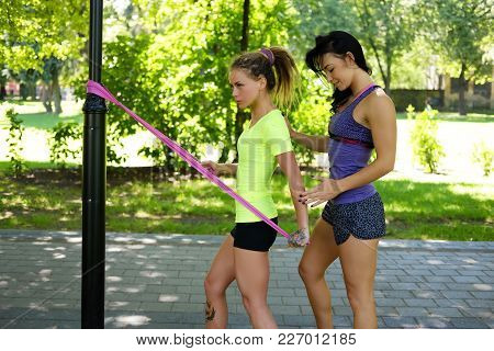 Sporty Females Doing Exercises With Fitness Trx Straps In Summer Park.