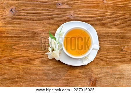 White Mug Of Tea On A Brown Wooden Table. Close Up, Top View