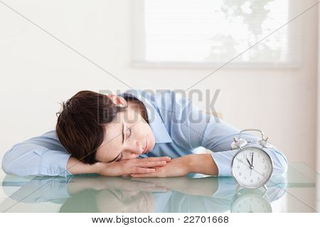 Sleeping Short-haired Woman With Her Head On The Desk Next To An