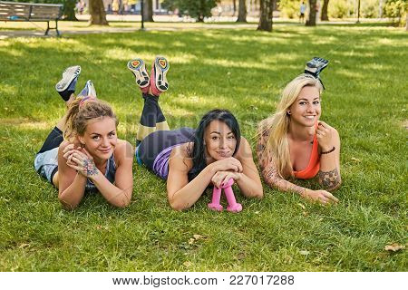 Three Attractive Sporty Females Lying On A Grass After Fitness Workouts In A Park.
