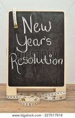 A Black Board With The Words New Years Resolution And A Measuring Tape