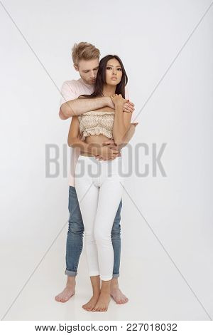 Romantic Young Mixed-race Couple Indoors In Studio Against White Background. Interracial Couple, Cau