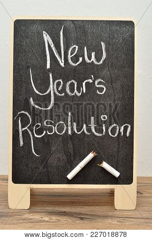 A Black Board With The Words New Years Resolution And A Cigarette Broken In Two