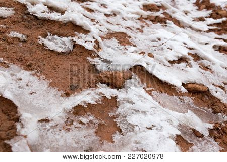 Snow On Red Clay In Nature . Photo Of An Abstract Texture