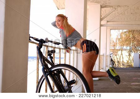 Sexy Blond Female In Sportswear Posing Near Bicycle.