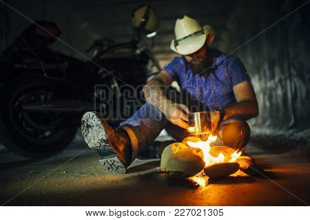 Man Drinking Coffee By The Fire At Night