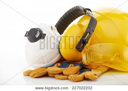 Yellow construction hard hat, earphones, goggles, respirator and gloves on a white background. Protective clothes.