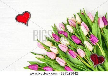 Pink Tulips With Red Hearts On White Wooden Background. Top View, Copy Space. Valentine Day, Wedding