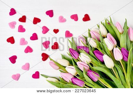 Tulips Bouquet With Pink Hearts On White Wooden Background. Top View, Copy Space. Valentine Day Conc