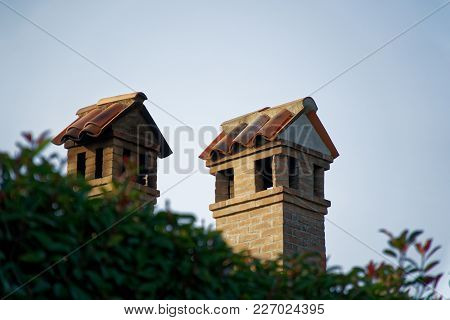 Chimneys Built Of Brick And Stainless Steel On A Tiled Roof, Italy Style.