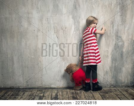 A Punished Child Standing By The Wall.