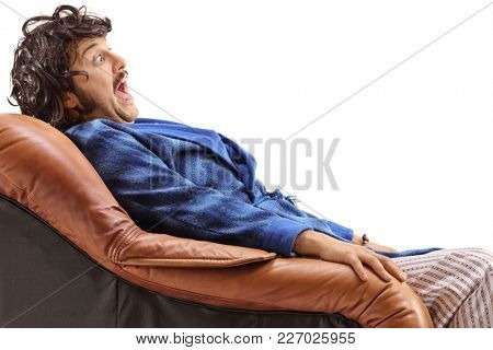 Terrified young man seated in an armchair isolated on white background