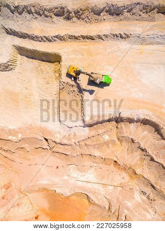 Aerial view of a working excavator in the open cast mine. Heavy industry and machinery. Industrial background on mining theme.