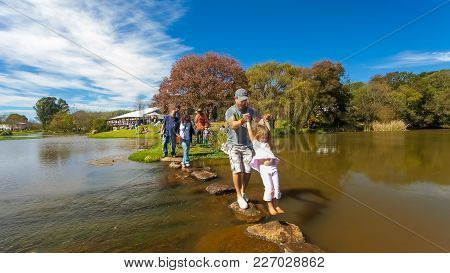 Johannesburg, South Africa, 05/10/2014,  Father And Daughter Crossing A Stream At The Winter Sculptu