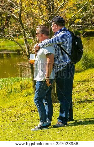 Johannesburg, South Africa, 05/10/2014, Gay Couple Enjoying A Moment Next To A Pond At The Winter Sc