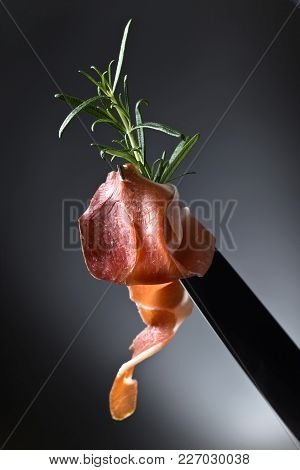 Prosciutto With Rosemary On A Knife Blade.
