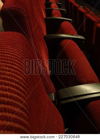 A Row Of Red And Black Chairs In An Auditorium