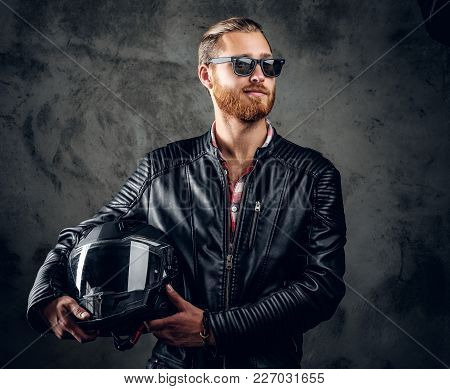 Portrait Of Redhead Male In Leather Jacket And Sunglasses Holds Motorcycle Helmet.