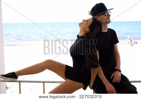 Sexy Female Posing With Her Boyfriend Over Blue Sea.