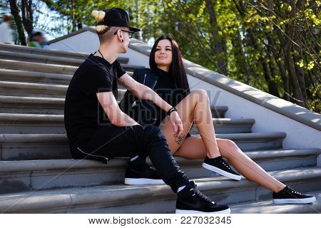 Casual Neordinary Couple Relaxing On Steps In A Park.