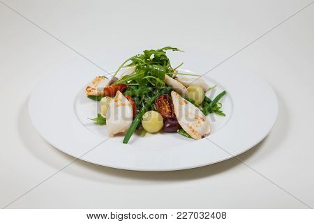 Seafood Salad With Tomato And Calamari On A White Plate On A White Background Isolated