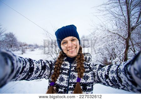 Cheerful Young Woman In Blue Hat And With Long Pigtails Makes Selfie On Smartphone