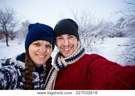 Smilling Young Couple In Beautiful Clothes Makes Selfie On Smartphone In Winter Park