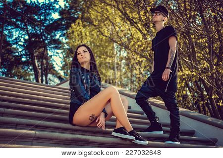 Modern Young Couple Posing On Stairs In Summer Park.