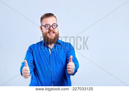 A Fat, Bearded Man With Glasses On A Gray Background With A Positive Stupid Expression Of Emotion.
