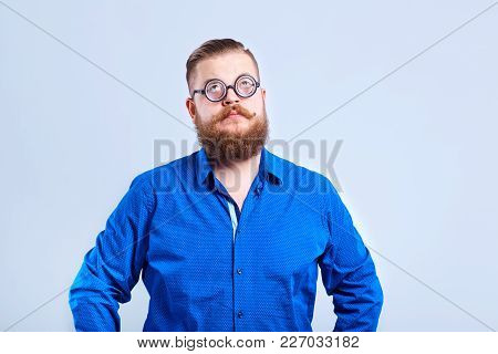 A Fat, Bearded Man Clever With Glasses On A Gray Background With A Clever Stupid Expression Of Emoti