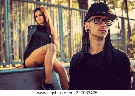 Portrait Of Unformal Man In A Cap With Sexy Lady On Background.