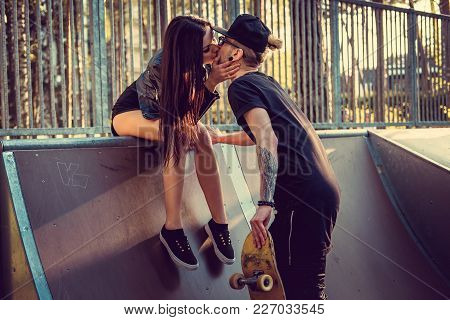 Sexual Brunette Kissing Tattooed Skater In Skate Park.