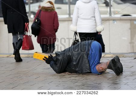 Homeless Man With Hurt Leg On His Knees Begs For Money At The Street. Ten Years After Joining The Eu