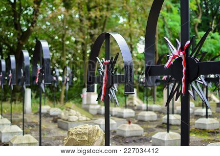 Ribbon With National Colours Of Poland Tied Up To The Cross On The Cemetery. Uprising Concept.