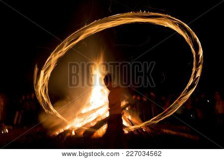 A Boy Spins Rings Of Fire Near A Bonfire During A Fire Ritual Celebration Of Sirni Zagovezni Held Se