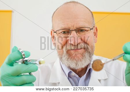Close Up Picture Of Senior Male Dentist Holding Dental Instruments - Anesthesic Syringe And Mirror