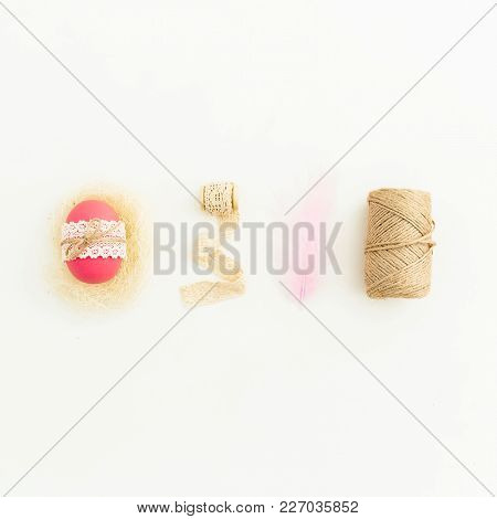Stylish Easter Composition With Pink Eggs With Twine, Feather And Tapes On White Background, Top Vie