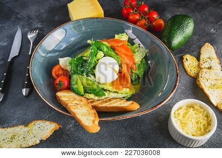 Caesar Salad With Egg, Salmon, Avocado, Cherry Tomatoes And Grilled Toast, Close Up View. Tasty Food