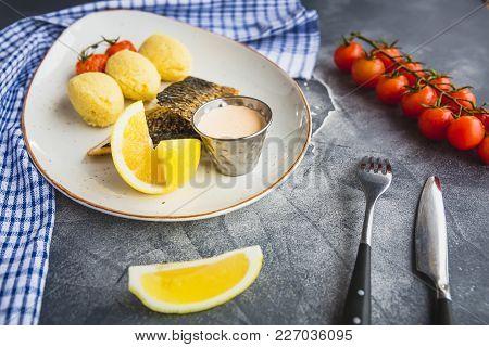 Fish Dish With Millet Porridge, Tomato, Lemon Slice And Shrimp Sauce On Dark Table