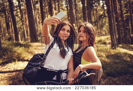 Two Females Making Selfie After Bike Riding In A Forest.