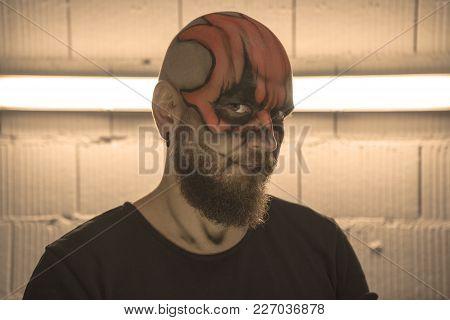 Make Up An Orange Skull. Portrait Of A Man Make Up A Skull. Bald Guy With Make Up. Bearded Bald Man