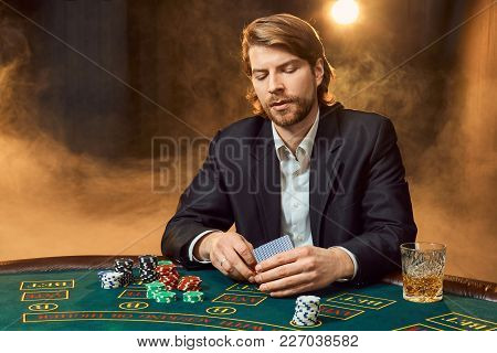 A Man In A Business Suit Sitting At The Game Table. Male Player. Passion, Cards, Chips, Alcohol, Dic