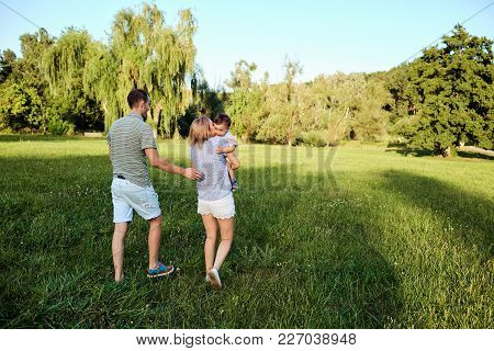 Happy Family In Nature. Parents With A Child Play In Park.