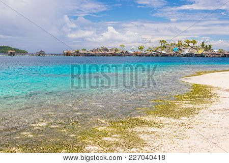 Tropical Beach, Turquoise Transparent Water And Lush Green Jungle In The Remote Togean (or Togian) I
