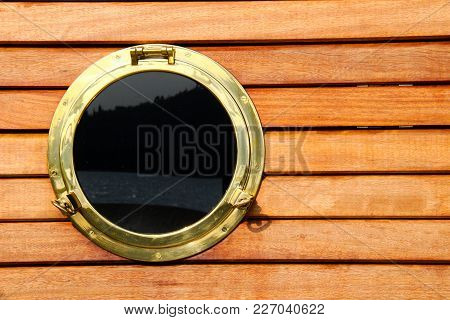 Porthole Made Of Golden Metallic Material. Background Made Of Wood