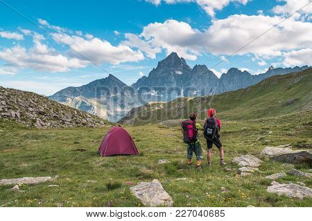 Couple Looking At The Majestic View Of Glowing Mountain Peaks At Sunset High Up On The Alps. Rear Vi