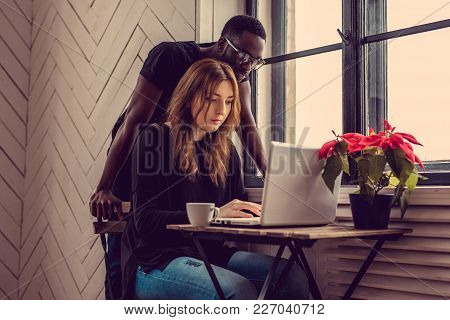African American Male And Caucasian Female Using Laptop At The Table.