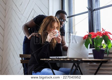 A Woman Drinking Morning Coffee And A Black Manin Eyeglasses Using A Laptop.